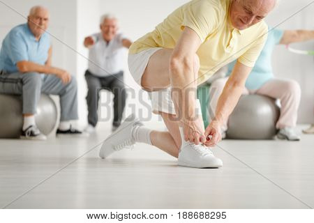 Close-up of older man preparing for workout on a gym