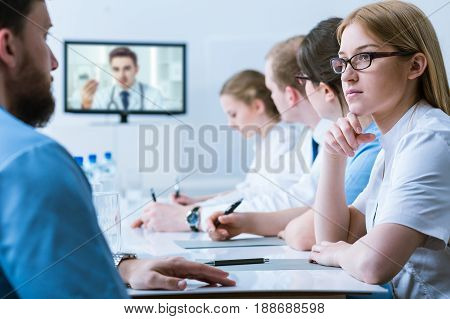 Hospital video conference for young doctors in scrubs and medical aprons