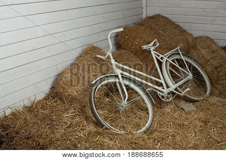 Old white bicycle with hay bale with retro effect