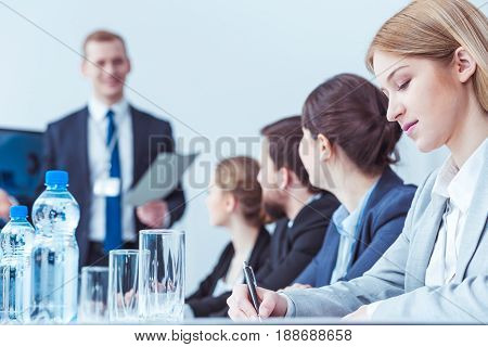 Elegant business lawyers writing during company board meeting