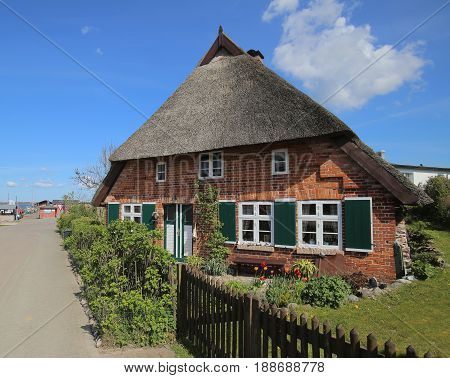 Street And Reed Roofed House In Stahlbrode In Mecklenburg-vorpommern. The Building Is A Listed Monum
