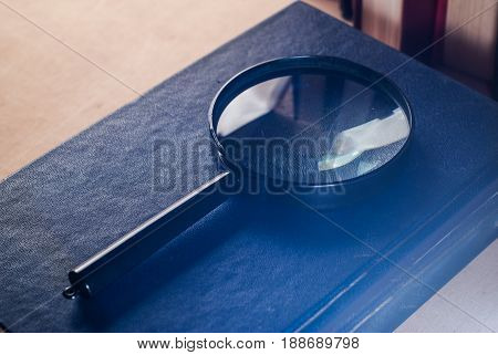 Magnifier with black handle is on the cover of the book, glare and reflections on the magnifying glass