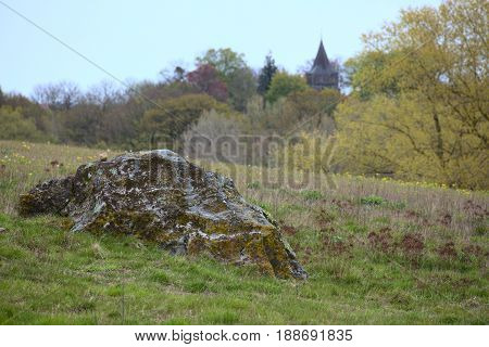 Erratic Block Near The Town Of Hohendorf In Mecklenburg-vorpommern. The Church Of The Town Can Be Se