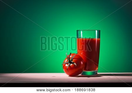 Glass of tomato juice and tomato on wooden table with green background