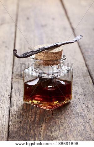 Bottle of homemade vanilla essence on wooden background