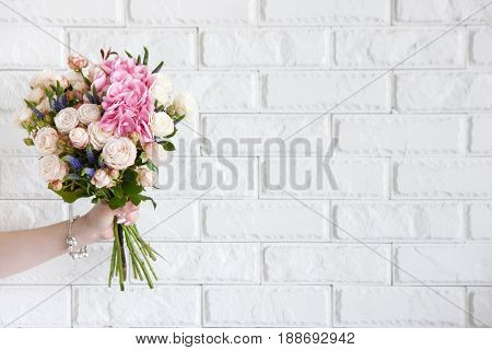Female hand show bouquet with rose flowers on white brick background. Gift for mother or woman, florist work, wedding decor, beautiful bouquet sale concept