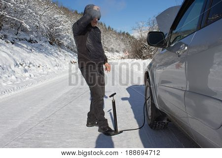 Inflating the tire of a Car. Man repairs bike in forest winter. Bicyclist pumping air into the wheel. Man uses a bicycle pump. Pumping air into an empty wheel of Man.