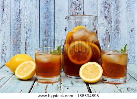 Pitcher Of Iced Tea With Two Glasses And Lemons On Rustic Blue Wood Background