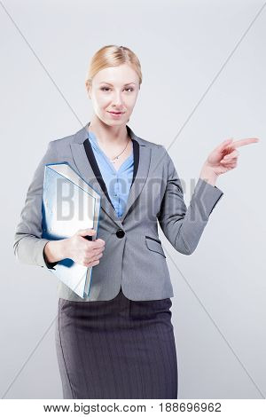 Young business woman with blue folder pointing her finger towards blank space isolated on grey background.