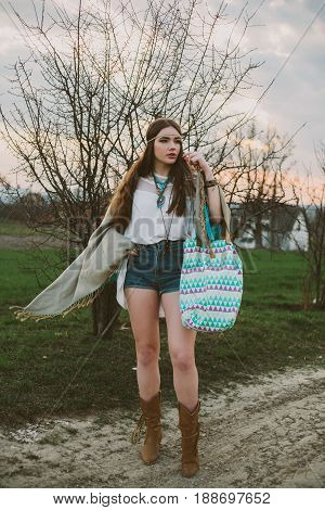 Hipster girl standing on a dirt road.indie
