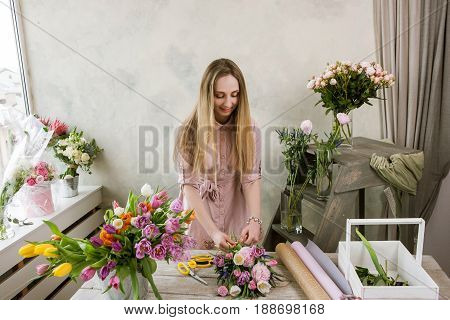 Florist in the workshop packs a bouquet. Decorator work with her creation. Woman in flower shop making floristry assemble