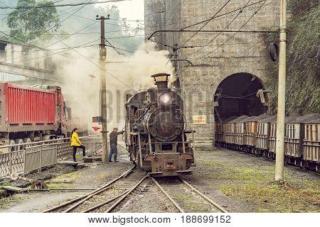 Yuejin Sichuan province China November 03 2016: Steam narrow-gauge locomotive stands by the platform before departure
