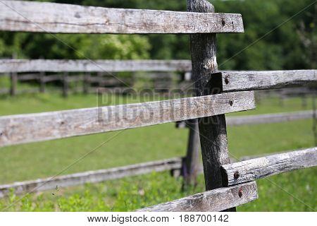 Old wooden rural corral fense in meadow