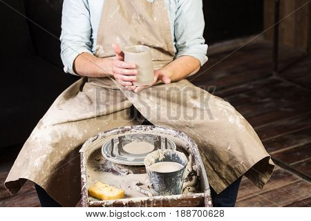 pottery, workshop, ceramics art concept - closeup on male hands holding unfired clay cup, a man examines a fresh product before further processing, master sits at the Potter's wheel, front view