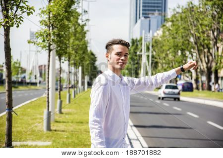 Young handsome man on side of a road, hailing and stopping a taxi cab