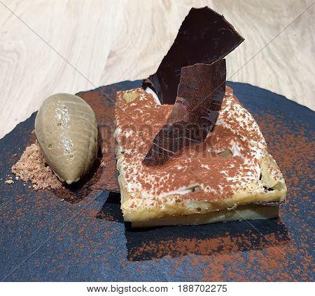 Belgian Speculoos Tiramisu Dessert. A gourmet European speculoos tiramisu professionally plated on a slate slab