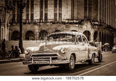 Havana, Cuba - September 14, 2016: American classic car drives on the main street with street life view in Havana Cuba - Retro Serie SEPIA Cuba Reportage