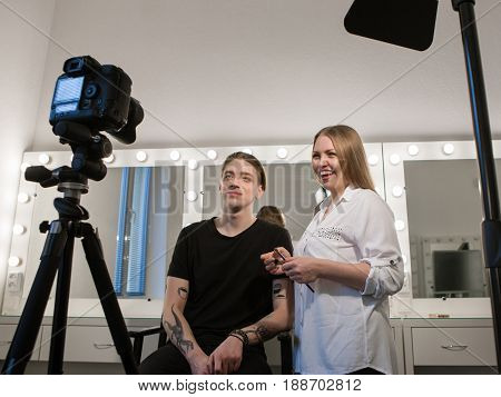 Horizontal indoors shot of female beautician and male model looking at camera after makeup applying. Video blogger backstage
