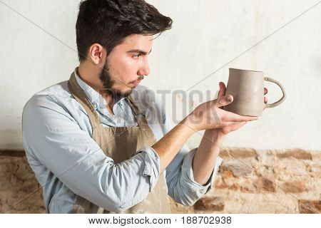 potter, workshop, ceramics art concept - ceramist holding cup and carefully examines the product, young male master dressed in a stained clay apron, craftsman's hands holding unbaked jug