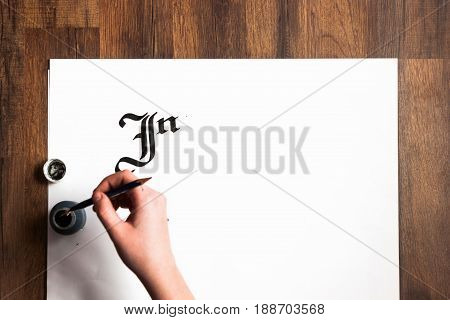 Lettering ink background. Unrecognizable painter's hand draws word inspire with inks on white paper. Drawing lessons, art school, creativity concept