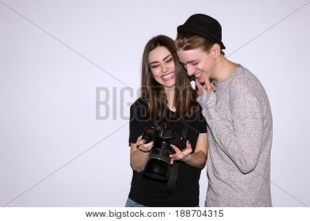 Happy couple enjoy with digital camera on white background. Female photographer show to male model photos. Woman and man laugh. Friendship of sexes, lifestyle, leisure, hobby concept