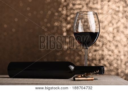 Glass filled with red wine near empty bottle and corkscrew on vintage wooden surface and on metallic bokeh background with copy space