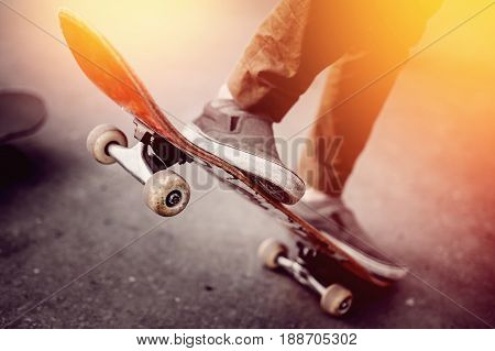 Close-up of a male guy on a skateboard doing trick kicks in shoes. The concept of doing street sports skateboarding. Sunset toning pictures.