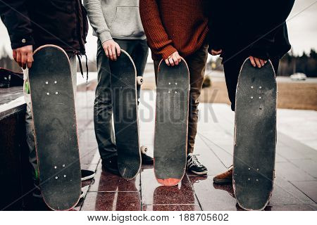 Friends of the men's company hold their hands skateboards. Concept group of street athletes students