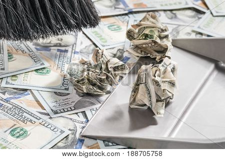 Broom sweeps crumpled dollars in the scoop from the surface covered with new dollars, close-up