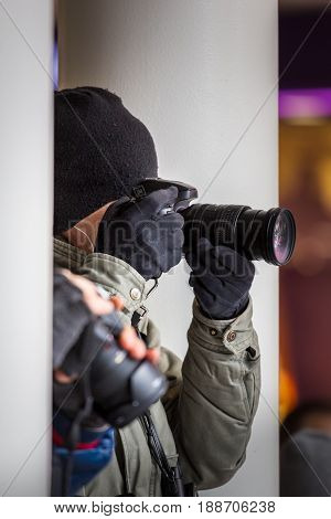 Paparazzi photographer hiding and taking pictures among buildings outdoors in the city. Authentic image of spy photograpy.