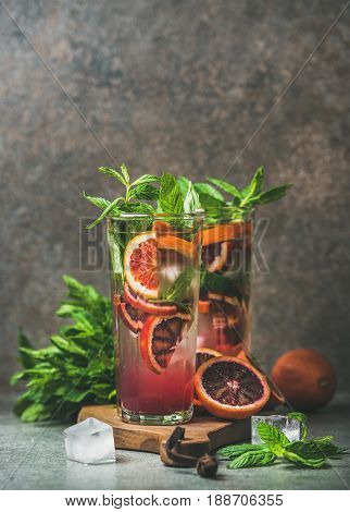 Blood orange citrus lemonade with mint and ice in tall glasses, dark brown stone background, copy space. Refreshing summer drink concept