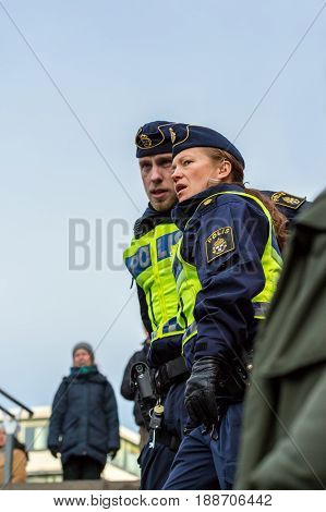 Policeman and police woman. Stockholm Sweden - January 21 2017: Low angle view of two police officers outdoors in a public place male and female. Talking and looking down. Slightly blurred women in the background.