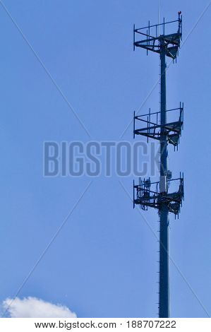 A single cell tower appears against the blue sky.