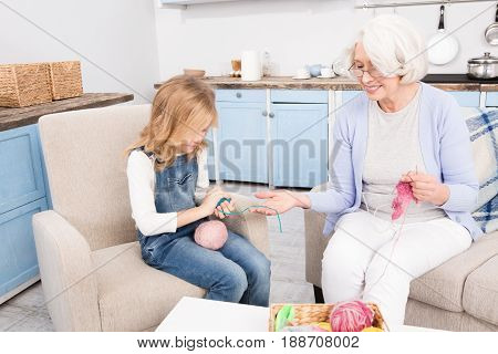 Granddaughter helping her granny to knit different kinds of clothes while sitting on sofa or couch. Granny teaching her grandchild.