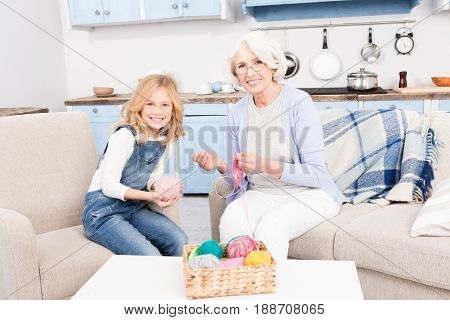 Grandmother knitting her grandchild new hat to give it as present or gift. Granddaughter and granny looking at camera and smiling.