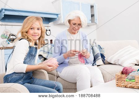 Grandmother knitting scarf to her granddaughter. Little lady holding ball of granddaughter winding ball of threads and looking at camera while sitting on arm chair.