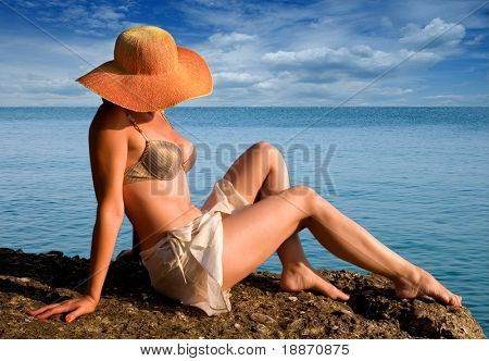 The woman in a hat against the sea