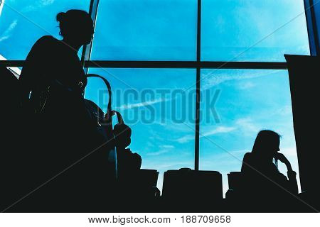 Silhouettes of people on the background of a window in the waiting room at the airport, people are waiting for their flight plane