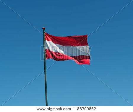 Flag of Austria on flagpole waving in the wind. Austrian national official flag on blue sky background. Patriotic symbol banner