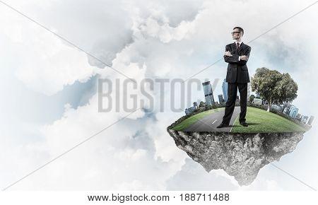 Elegant confident businessman standing on green floating island in blue sky