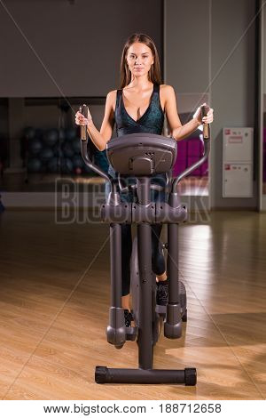 Attractive young woman is working out on an elliptical trainer in gym