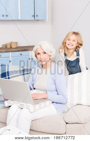 Granddaughter teaching her grandmother how to play on computer. Happy granny using laptop computer. Happy ladies smiling for camera.