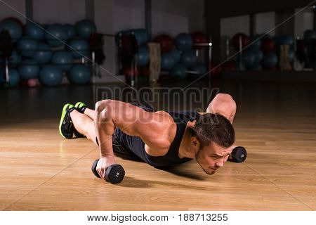 Young Man Athlete Doing Pushups With Dumbbells As Part Of Bodybuilding Training