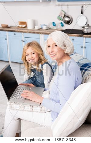 Granddaughter teaching her grandmother how to search in Internet. Happy grandmother and her grandchild smiling and looking at camera.