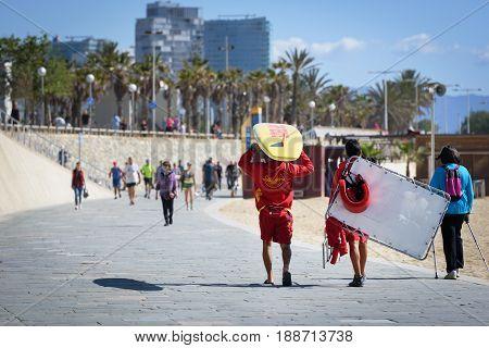 BARCELONA, SPAIN - MAY 2017: Beach lifeguard men are walking along the promenade of Barceloneta beach
