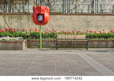 Tulip shaped public phone and wooden bench in front of built-in tulip flower box and grunge wall on tiled stone floor Fatih district Istanbul Turkey
