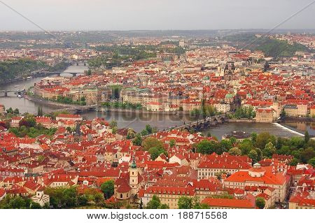 Panoramic view on old antique part of Prague city in Czech Republic. Classic orange terracotta buildings houses roofing, Praha I Charles bridge, cathedral, Vltava river, park. Famous sightseeing tours