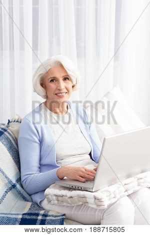Elderly woman keeping record of finances in laptop. Happy woman smiling for camera while sitting on sofa or couch. Computer technologies concept.