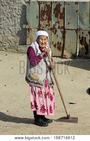 Aral, Kazakhstan - April 24, 2017: Kazakh country old woman in traditional clothes working with hoe