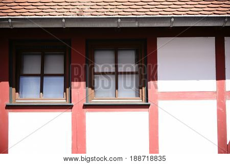 The close-up of the beam construction of a half-timbered house with windows in strong sunlight under the roof.